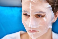 Mulher em uma máscara facial de papel fotografia de stock