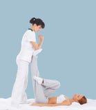 Mulher em uma massagem tailandesa em um fundo ciano imagem de stock