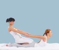 Mulher em uma massagem tailandesa em um fundo ciano fotos de stock royalty free