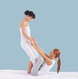 Mulher em uma massagem tailandesa em um fundo ciano imagens de stock