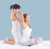 Mulher em uma massagem tailandesa em um fundo ciano imagens de stock royalty free