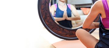 Mulher em uma pose da ioga na frente de um espelho Imagem de Stock