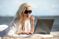 Mulher em uma praia com um portátil Fotografia de Stock