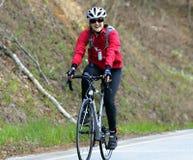 Mulher em uma raça de bicicleta Imagens de Stock