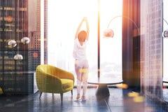 Mulher em uma sala de visitas amarela da poltrona Imagens de Stock Royalty Free