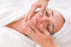 A mulher em uns termas está começ uma massagem em sua face Imagem de Stock Royalty Free