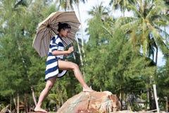 Mulher em vestido listrado com guarda-chuva que anda em rochas Imagem de Stock