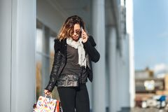 Mulher em vidros de sol um casaco de cabedal preto, calças de brim pretas com sacos de compras falando no telefone celular na fre Fotografia de Stock Royalty Free