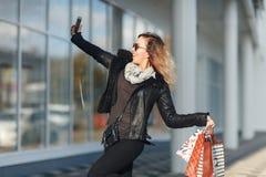 Mulher em vidros de sol um casaco de cabedal preto, calças de brim pretas que guardam um grupo dos sacos de compras que fazem Sel Imagens de Stock