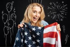 Mulher emocional feliz que guarda a bandeira americana Imagem de Stock
