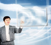 A mulher empurra botões da tela de toque contra o fundo natural azul Imagem de Stock