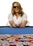 A mulher empurra microplaquetas de póquer na tabela de feltro do azul Imagem de Stock Royalty Free