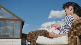 A mulher encantador leu o livro na cadeira de vime e relaxou no quintal da casa de campo filme