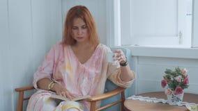 Mulher encantador nova que senta-se no livro da cadeira e de leitura ao lado da janela em casa video estoque