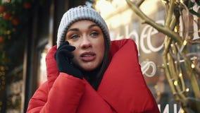 A mulher encantador olha a fala feliz no telefone quando estiver na rua fria do inverno video estoque