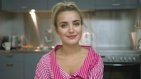 Mulher encantador que olha a câmera na cozinha vídeos de arquivo