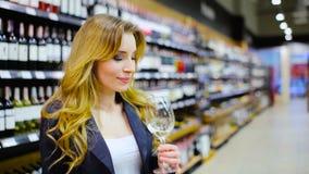Mulher encantador que prova um vinho branco na loja de vinho filme