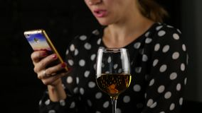 A mulher encantador usa o telefone celular e bebe o vinho branco a senhora bonita que comemora e envia uma mensagem Movimento len vídeos de arquivo