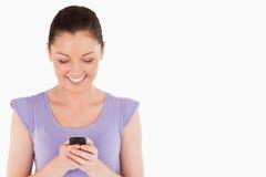 Mulher encantadora que escreve um texto em seu telefone Fotos de Stock Royalty Free