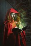 Mulher encapuçado vermelha com livro mágico