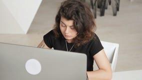 A mulher encaracolado com tatto e perfurações está trabalhando seriamente no computador video estoque
