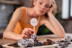 Mulher encaracolado-de cabelo virada que é aflição com chocolate proibido imagens de stock royalty free