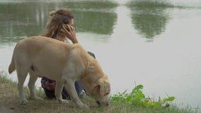 A mulher encaracolado e Labrador estão descansando perto do rio video estoque