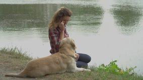 A mulher encaracolado e Labrador estão sentando-se perto do lago filme