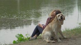 A mulher encaracolado e Labrador estão sentando-se perto do lago de volta à parte traseira vídeos de arquivo