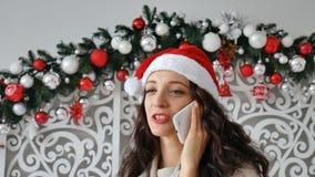 Mulher encaracolado escura alegre que veste o chapéu de Santa com a expressão retirada da cara que fala no telefone, sorrindo sin filme