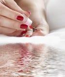Mulher, encerrando o verniz nos pés Fotografia de Stock Royalty Free