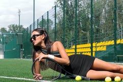 A mulher encontra-se em um jogador de tênis da grama com uma raquete em suas mãos Foto de Stock