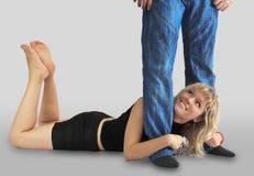 A mulher encontra-se entre os pés no homem Fotografia de Stock Royalty Free