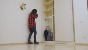 A mulher encontram o homem dentro do armário e assustado da surpresa video estoque
