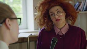 Mulher engraçada do tédio na peruca vermelha que dá a entrevista no microfone video estoque