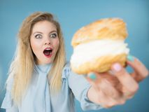 A mulher engraçada guarda o bolo do sopro de creme Imagem de Stock Royalty Free