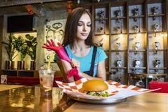 Mulher engraçada loura nova que come um Hamburger no caf exterior imagem de stock