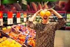 Mulher engraçada que guarda a toranja para seus olhos Compra da jovem mulher para ingredientes da receita em um supermercado que  foto de stock