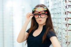 Mulher engraçada que tenta muitos quadros dos monóculos na loja ótica Foto de Stock Royalty Free