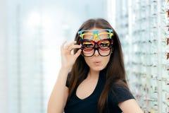 Mulher engraçada que tenta muitos quadros dos monóculos na loja ótica Fotos de Stock