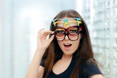 Mulher engraçada que tenta muitos quadros dos monóculos na loja ótica foto de stock