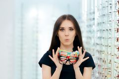 Mulher engraçada que tenta muitos quadros dos monóculos na loja ótica Imagem de Stock