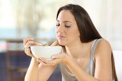 Mulher enojado que come cereais com mau gosto Imagens de Stock Royalty Free