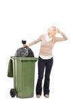 Mulher enojado que está ao lado de um balde do lixo Fotografia de Stock