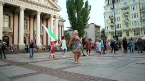 A mulher ensina a povos danças populares no quadrado principal, eventos do ar livre, bandeira nacional de Bulgária filme