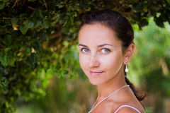 Mulher entre arbustos verdes Imagem de Stock Royalty Free