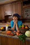 Mulher entre os vegetais na cozinha foto de stock