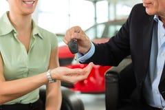 A mulher entrega chaves do carro ao homem no auto negociante Foto de Stock