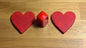 A mulher entrega a colocação de duas formas vermelhas do coração e a iluminação acima de uma vela Amor, romance, dia do ` s do Va filme