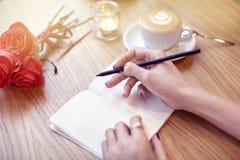 A mulher entrega a escrita do close-up no caderno, usando o lápis, páginas vazias para a disposição Café do latte do cappuccino c Fotos de Stock
